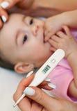 Zieke baby die koorts worden gecontroleerd. royalty-vrije stock afbeeldingen