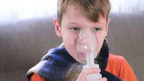 Zieke blonde jongen die door inhaleertoestelmasker inhaleren Gebruiksverstuiver en inhaleertoestel voor de behandeling stock video