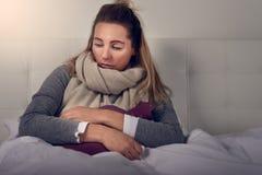 Zieke die vrouw in een warme sjaal wordt verpakt en het clutching van een warm waterfles stock foto's