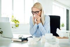Zieke en overwerkte onderneemster in het bureau, die haar nrs. blazen stock foto's