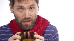 Zieke gebaarde hipster met koude en dranken hete thee met citroen stock footage