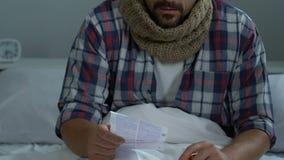 Zieke hoestende mens in de pilleninstructie van de bedlezing, griepsymptoom, gezondheidszorg stock footage
