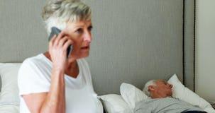 Zieke hogere man die op bed liggen terwijl vrouw die op mobiele telefoon spreken stock videobeelden