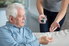 Zieke hogere mens die geneeskunde nemen Stock Foto's