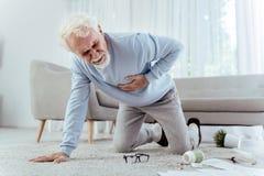 Zieke hogere mens die van hartaanval vallen royalty-vrije stock afbeelding