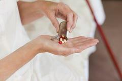 Zieke hogere vrouw die haar pillen neemt stock fotografie
