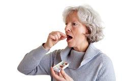 Zieke hogere vrouw die medicijn neemt Stock Foto