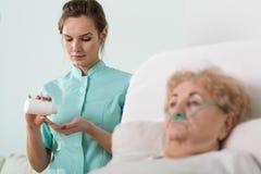 Zieke hogere vrouw en verpleegster Royalty-vrije Stock Foto's