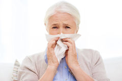 Zieke hogere vrouwen blazende neus aan document servet royalty-vrije stock foto