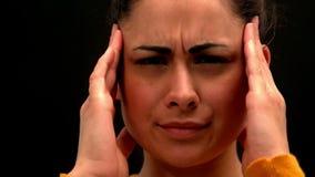 Zieke jonge vrouw die haar hoofd op zwarte achtergrond wrijven stock videobeelden