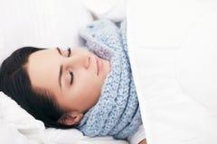 Zieke jonge vrouw die in het bed thuis rusten Stock Foto's