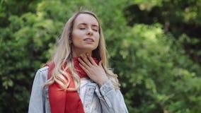 Zieke jonge vrouw die rode sjaal dragen die het slechte lijden aan keelpijn voelen, keelpijn, die zich in het park bevinden pijnl stock footage