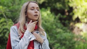 Zieke jonge vrouw die rode sjaal dragen die het slechte lijden aan keelpijn voelen, die zich in het park bevinden Het pijnlijke S stock video