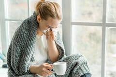 Zieke jonge vrouw met koude en griep thuis stock foto