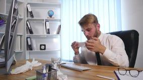 Zieke jonge zakenman die zijn neus blazen in zakdoek stock footage