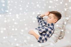 Zieke jongen die in bed liggen en aan hoofdpijn lijden Royalty-vrije Stock Foto