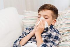 Zieke jongen die in bed liggen en zijn neus thuis blazen stock fotografie