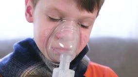 Zieke jongen die door inhaleertoestelmasker inhaleren Gebruiksverstuiver en inhaleertoestel voor de behandeling stock videobeelden
