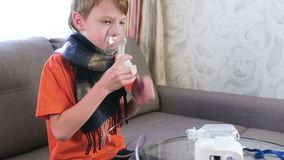 Zieke jongen die door inhaleertoestelmasker inhaleren Gebruiksverstuiver en inhaleertoestel voor de behandeling stock video