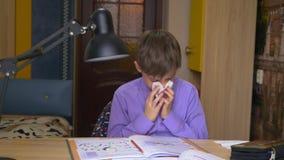 Zieke jongen die zijn neus blazen in een servet terwijl thuis het zitten bij een lijst stock videobeelden