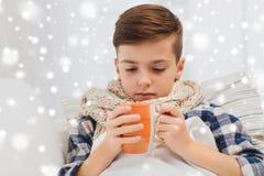Zieke jongen met griep in sjaal het drinken thee thuis Stock Foto's