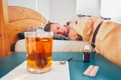 Zieke mens in bed stock foto's