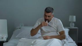 Zieke mens in bed die neusdalingen in neus zetten en in slaap ziektebehandeling vallen stock video