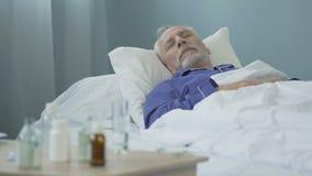 Zieke mens die dosis die geneesmiddelen nemen en rust hebben, in bed, dagslaap liggen stock videobeelden