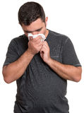 Zieke mens die zijn die neus blazen op wit wordt geïsoleerd stock foto