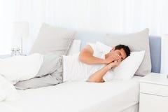 Zieke mens die zijn neus blaast die op zijn bed ligt Royalty-vrije Stock Afbeeldingen