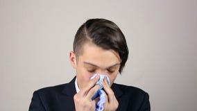 Zieke mens die zijn neus blazen in een weefsel stock footage