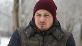 Zieke mens die zijn neus in de winterpark blazen stock video