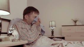 Zieke mens die zijn neus in het bed blazen stock video
