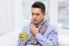 Zieke mens met griep het drinken thee en thuis het hoesten Royalty-vrije Stock Afbeeldingen