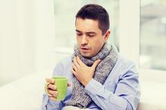 Zieke mens met griep het drinken thee en thuis het hoesten Stock Fotografie