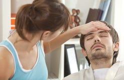 Zieke mens met koorts in bed Royalty-vrije Stock Afbeelding