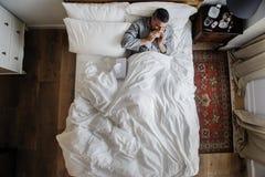 Zieke mens op het bed die zijn neus blazen stock foto
