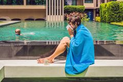 Zieke mensenreiziger De man ving een koude op vakantie, zit droevig bij de pool het drinken thee en blaast zijn neus in een serve royalty-vrije stock foto's