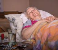 Zieke oude vrouw die in bed thuis liggen Royalty-vrije Stock Fotografie