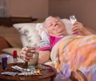 Zieke oude vrouw die in bed thuis liggen Royalty-vrije Stock Afbeeldingen