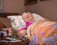 Zieke oude vrouw die in bed thuis liggen Royalty-vrije Stock Foto's