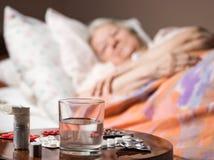 Zieke oude vrouw die bij bedbed liggen Royalty-vrije Stock Fotografie