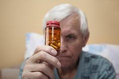 Zieke oudste met pillen Stock Foto