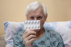 Zieke oudste met pillen Stock Foto's