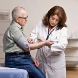 Zieke patiënt die genomen bloeddruk heeft Stock Foto