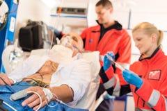 Zieke patiënt met paramedicus in ziekenwagenbehandeling Stock Afbeelding
