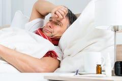 Zieke rijpe mens op bed Stock Afbeelding
