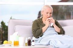 Zieke rijpe vrouw die aan hoest thuis lijden stock fotografie