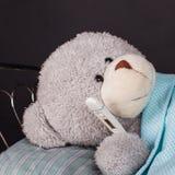 Zieke teddybeer die in bed met een temperatuur liggen stock fotografie