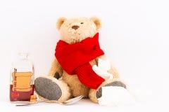 Zieke teddybeer met uitstekende geneeskundefles op witte achtergrond royalty-vrije stock afbeelding